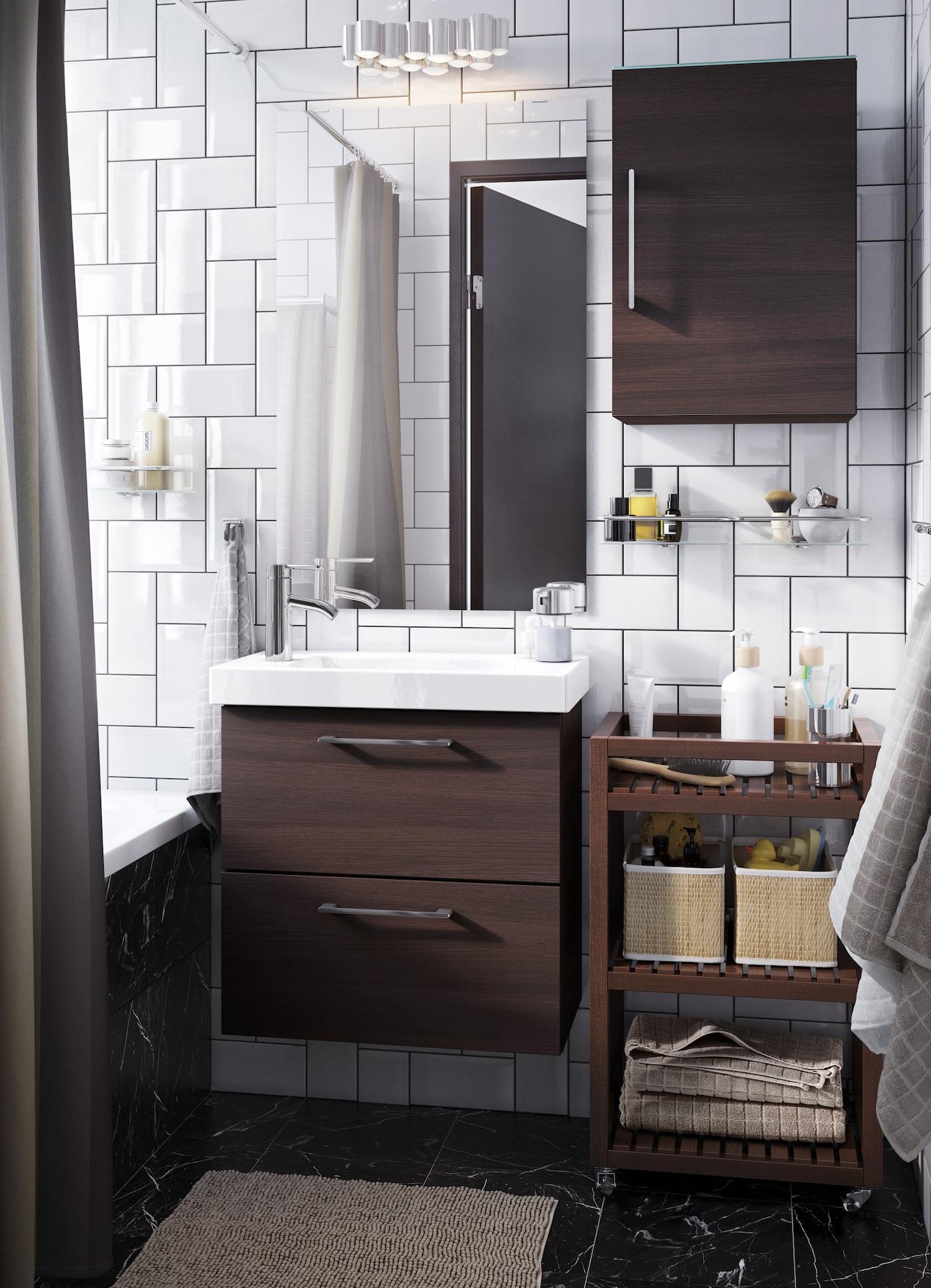 Pieni valkoinen kylpyhuone, jossa tummanruskeaa avointa ja suljettua säilytystilaa.
