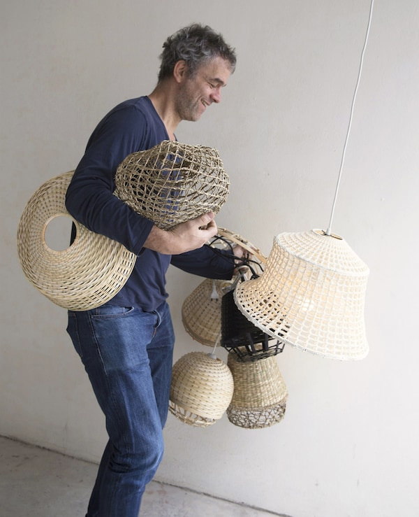 Piet Hein Eek carrying bamboo lampshades.