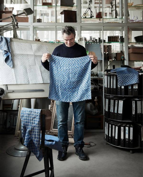 Piet Hein Eek holding up patterned blue textiles.