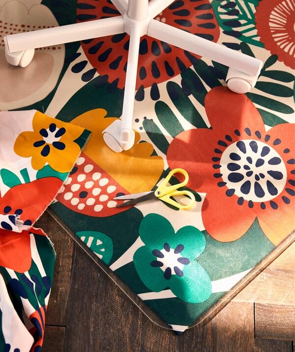 Piètement à roulettes sur un protecteur de sol personnalisé avec du tissu à motif floral multicolore.