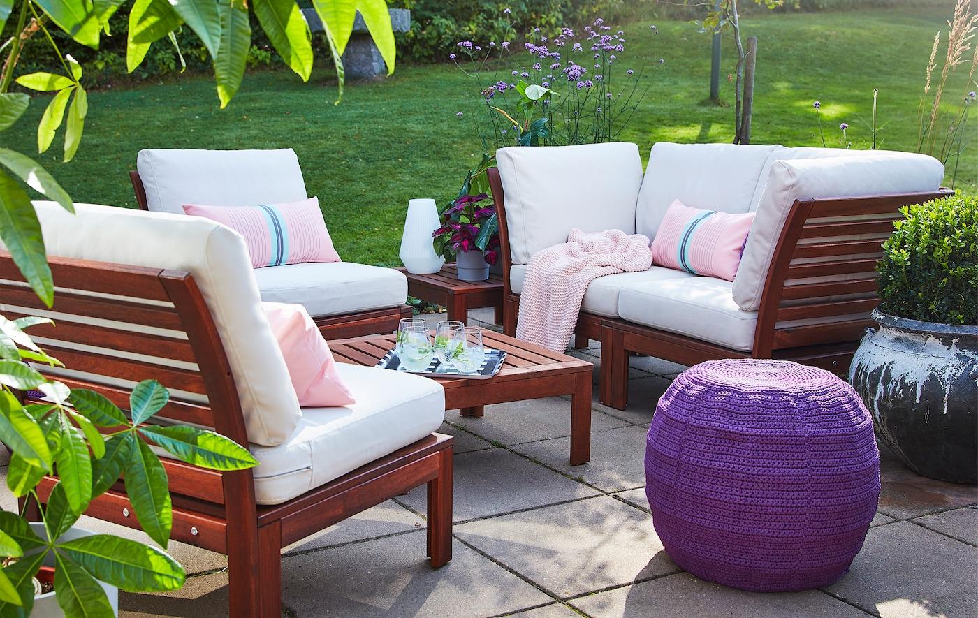 Pihalla kivilaattojen päällä istuinryhmä, jonka puisilla sohvalla ja kahdella tuolilla valkoiset istuintyynyt.
