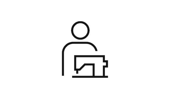 Piktogram osoby za šicím strojem symbolizující službu šití na přání