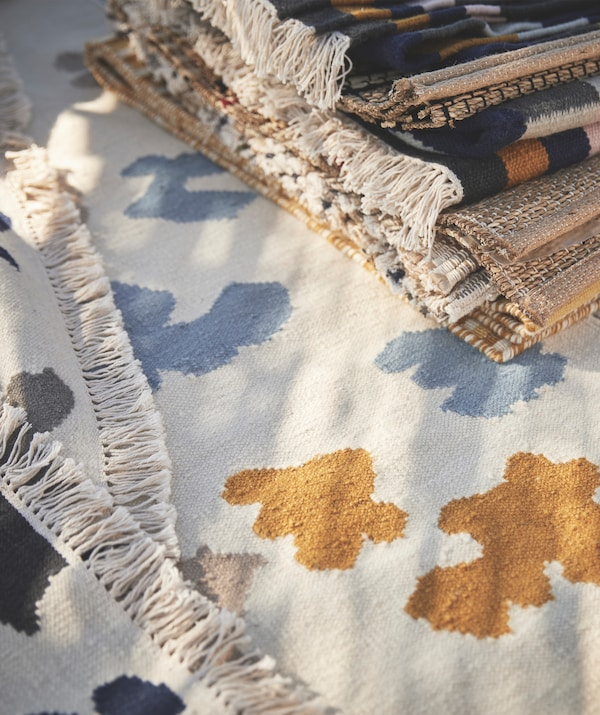 Pile de tapis déposée sur un tapis à motif bleu et jaune sur fond blanc.