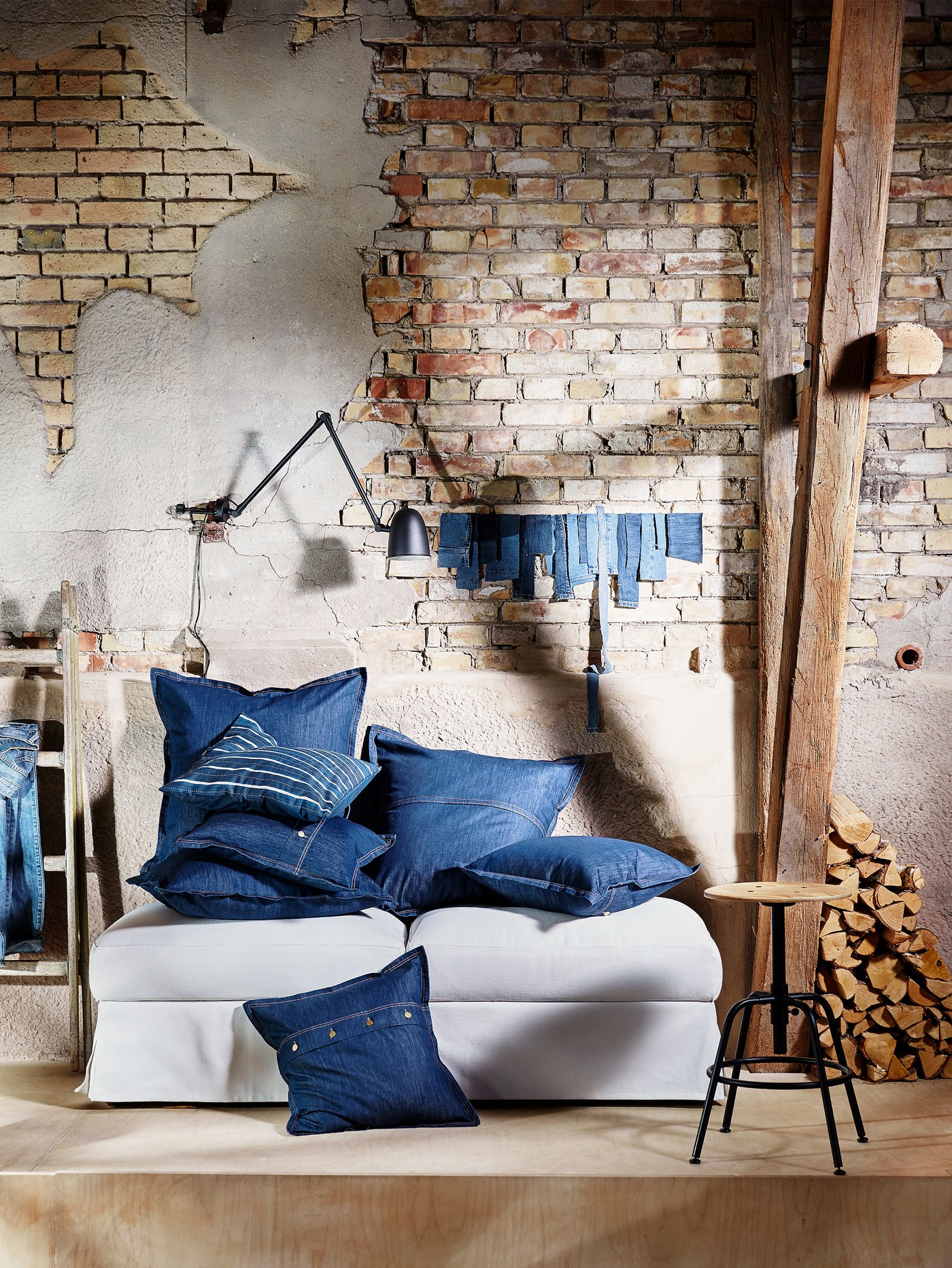 Piled on a sofa, in front of a brick wall, square denim SISSIL cushion covers with details like buttons and jean-like seams.
