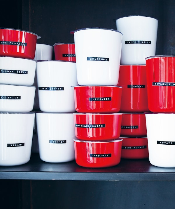 Piles de pots rouges et blancs étiquetés, contenant des ingrédients secs.