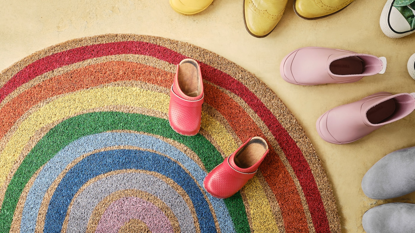 PILLEMARK door mat with a colourful rainbow pattern lying on a floor surrounded by shoes.