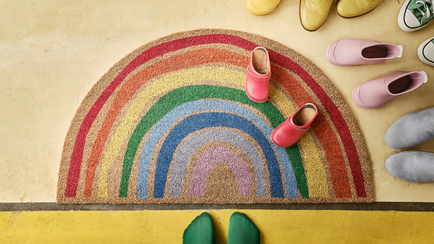 PILLEMARK door mat with a rainbow pattern lying on a floor with colourful shoes and a pair of feet with socks.
