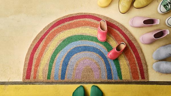 PILLEMARK Fussmatte mit einem fröhlichen Regenbogenmuster auf einem hellen Boden. Drumherum stehen Schuhe.