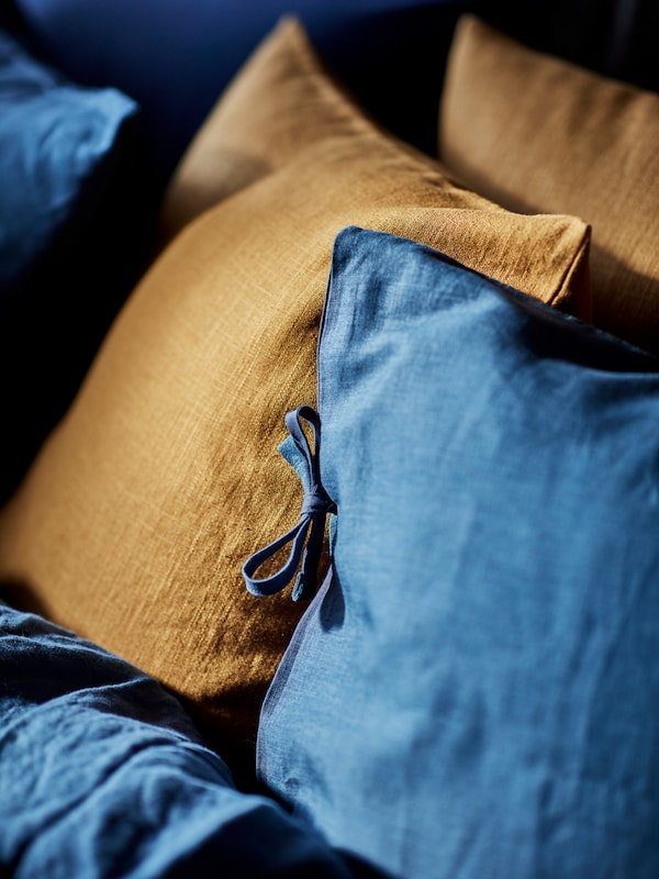 Pillows with dark blue PUDERVIVA pillowcases mixed with pillows with light yellow PUDERVIVA pillowcases.