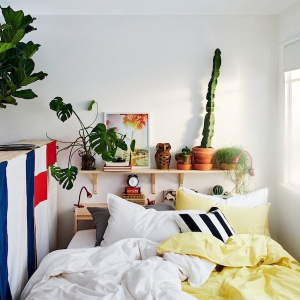 Pine, TARVA bed frame dressed with white and pale yellow ÄNGSLILJA bed textiles, against a white wall with aspen shelves