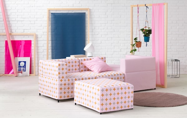 Pink and patterned modular sofa in a white room.