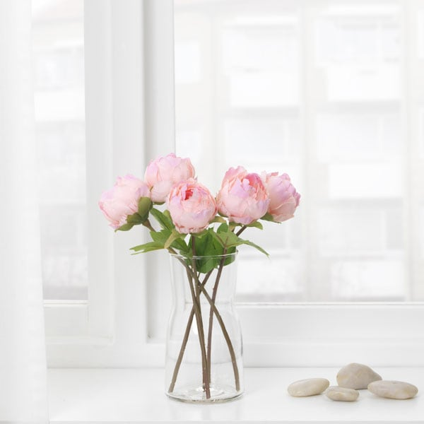 Pink artificial peony in glass vase