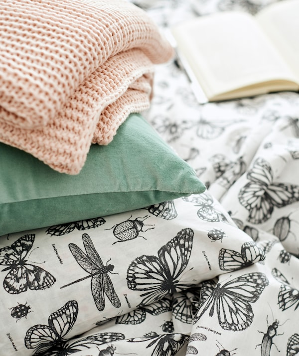 Pink knitted throw and green velvet cushion piled on top of a duvet and matching pillowcase with insect illustration design.