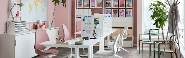 Pink office interior with two white work desks in the middle and pink and white office chairs.