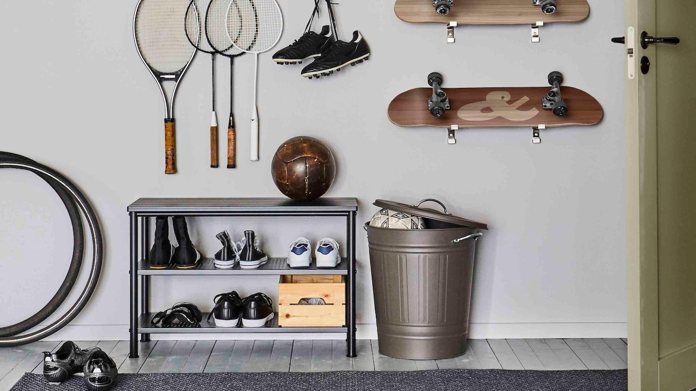 PINNIG bänk med skoförvaring och en fotboll i och intill en KNODD tunna med öppet lock. På väggen ovanför hänger racketar och skateboards.
