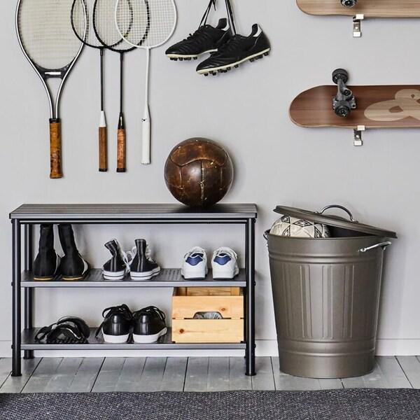 PINNIG-kenkäteline, jossa kenkiä ja jalkapallo, kannella varustetun KNODD-sangon vieressä. Mailoja ja rullalautoja seinällä yläpuolella.