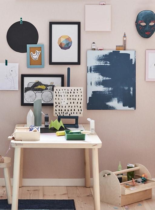 Pinturas y dibujos exhibidos en una pared rosa sobre un escritorio de madera clara.