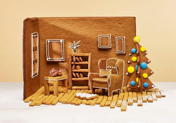 Piparkakkutalon sisällä, piparista valmistetut nojatuoli, hylly, pöytä ja joulukuusi.