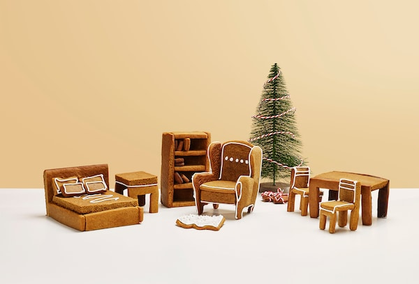 Piparkakuista valmistettuja minikalusteita ja joulukuusi keltaista taustaa vasten.