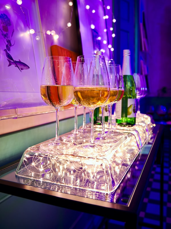Pirofila in vetro MIXTUR capovolta, con sotto l'illuminazione a LED VISSVASS, a formare un vassoio luminoso per i bicchieri di vino - IKEA