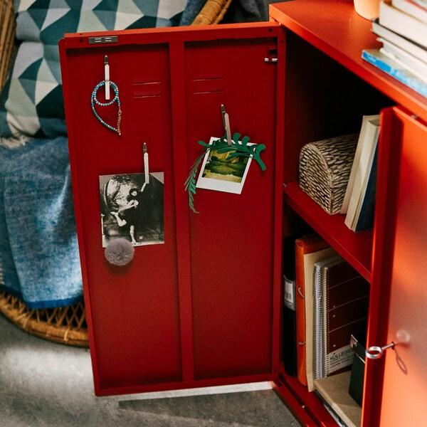 Piros IVAR szekrény félig nyitva, benne könyvekkel.