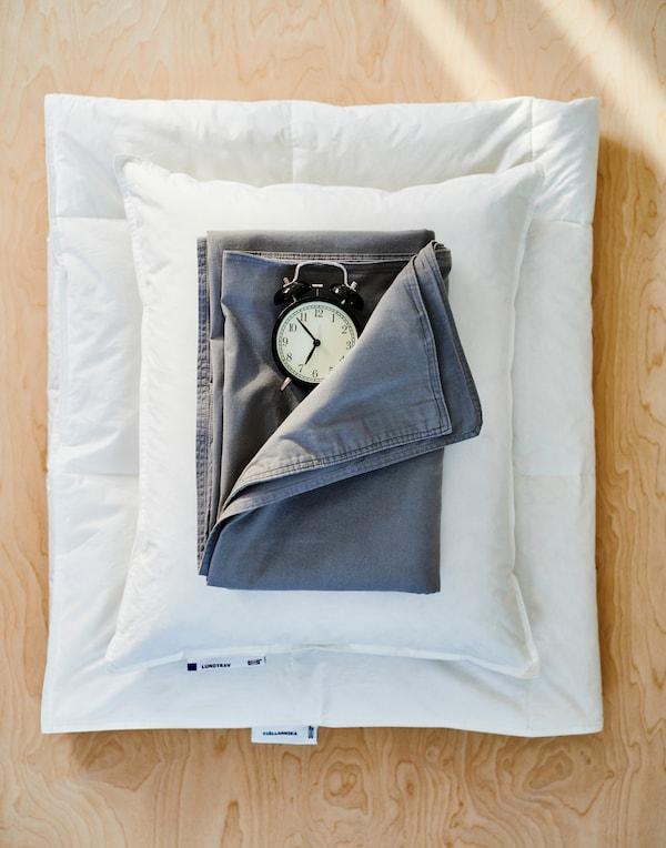 Piumino bianco piegato, cuscino bianco, lenzuolo blu scuro e una sveglia nera dallo stile vintage, su una superficie in legno.