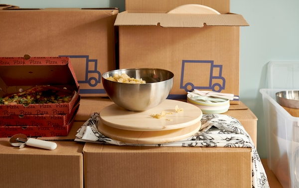 Pizzas in cartons and a lazy Susan with snacks in a BLANDA BLANK bowl on it placed on stacks of JÄTTENE packaging boxes.