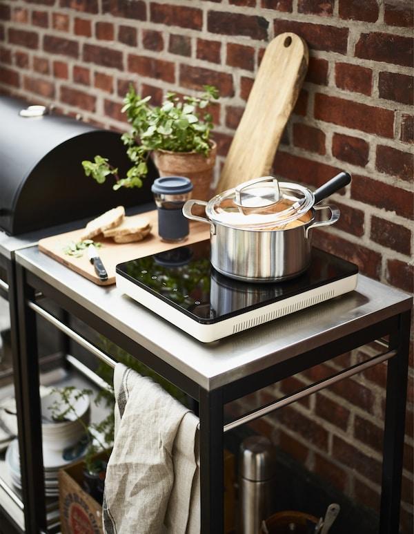 Placa de inducción portátil con una cacerola y una taza IKEA PS 2017 con tapa junto a la barbacoa en una terraza.