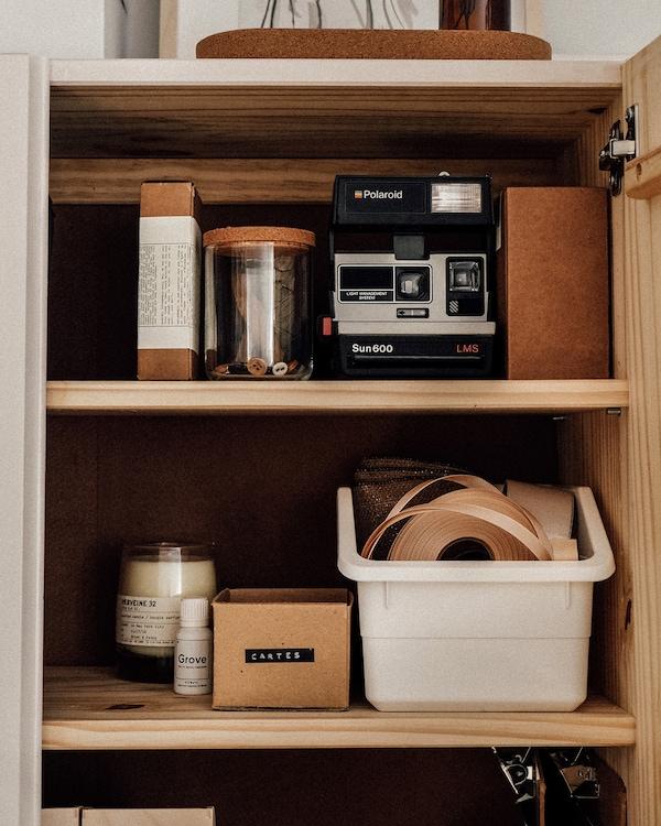 Placard IVAR rempli de divers objets artisanaux et d'un appareil photo.
