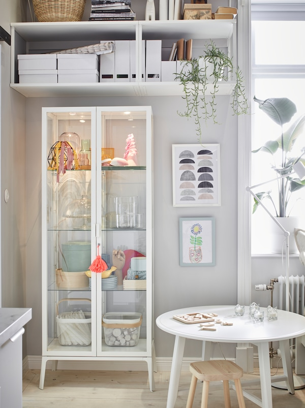 Placed in a corner, a tall, white MILSBO cabinet with display storage stands underneath high, wall shelves with more storage.