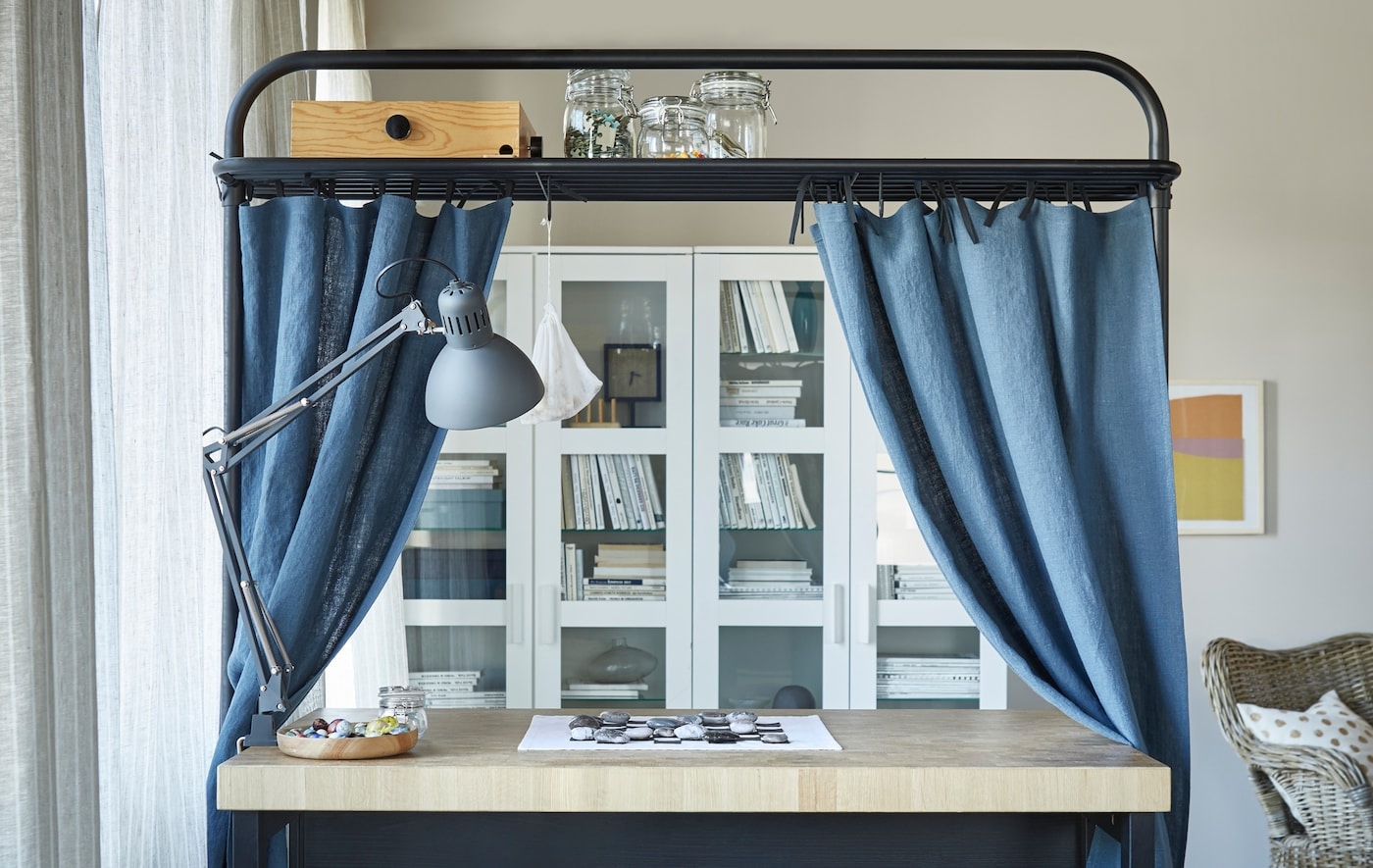 Placed in the living room, the island becomes an ideal spot for homework, board games and more. Here the overhead frame serves both as storage space and rod for functional, decorative curtains.