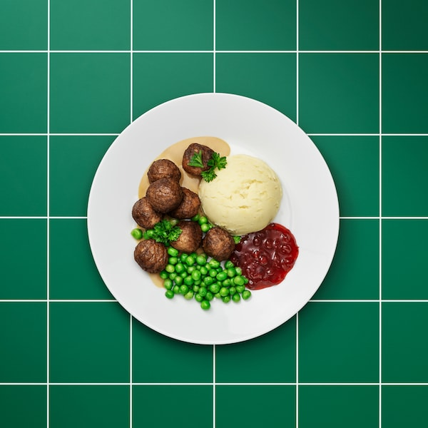 Plain white plate of plant balls, brown sauce, mashed potatoes, lingonberry jam, green peas and a sprig of parsley.