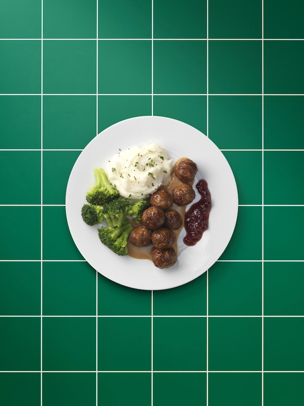 Plain white plate of plant-based meatballs, brown sauce, mashed potatoes, lingonberry jam, brocolli and a sprig of parsley.