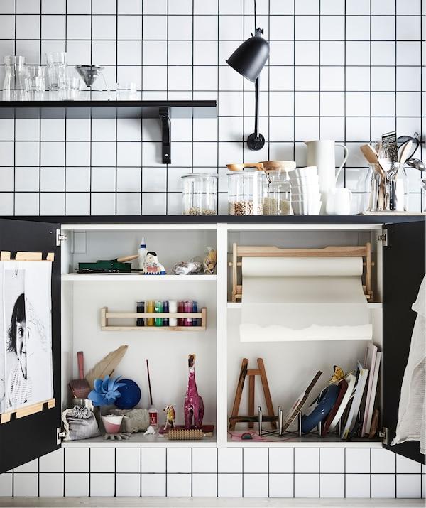 Plan de travail de cuisine avec en dessous deux portes d'armoire ouvertes, révélant un atelier d'art miniature caché à l'intérieur.