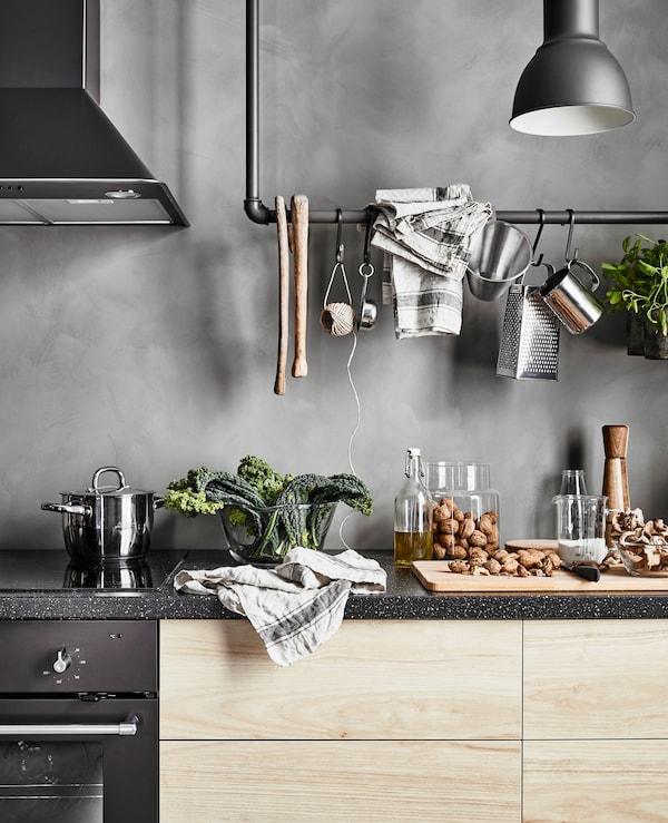 Plan de travail motif granit et tiroirs en imitation frêne, à côté d'une table de cuisson, d'un four et d'une hotte