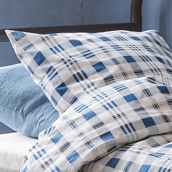 Plan rapproché de la housse de couette à carreaux bleus et d'un oreiller.