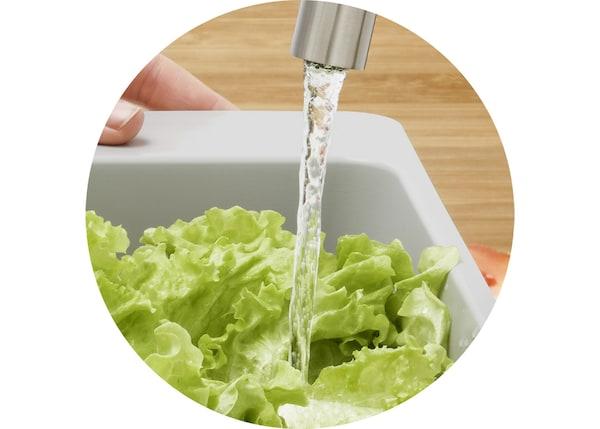 Plan rapproché d'eau qui coule sur de la laitue verte.