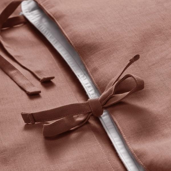 Plan rapproché d'une boucle décorative sur une taie d'oreiller PUDERVIVA rose foncé.