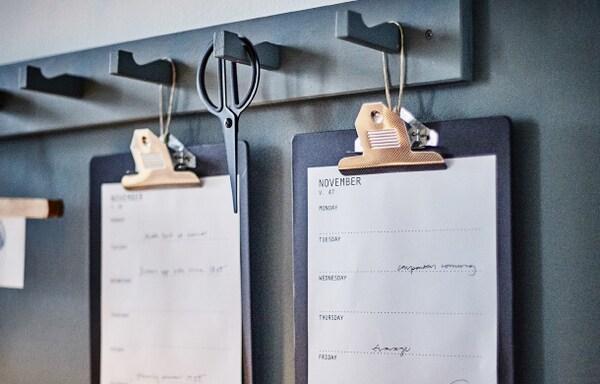 Planchettes à pince VÄLBEKANT et calendrier accrochés aux patères.