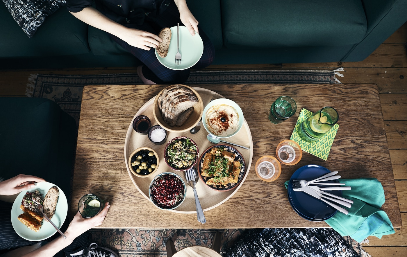 Plano cenital de gente disfrutando de una comida de estilo marroquí servida en una mesa de centro.