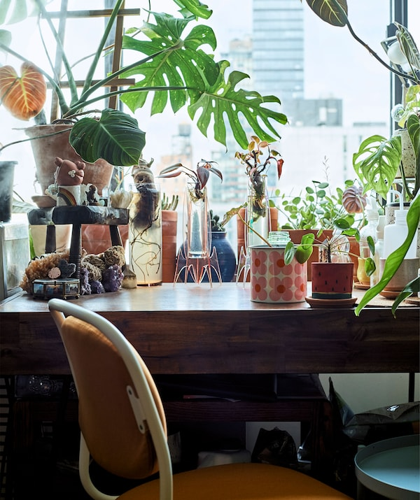 Plant pots and vases on a wooden desk with an orange swivel desk chair.