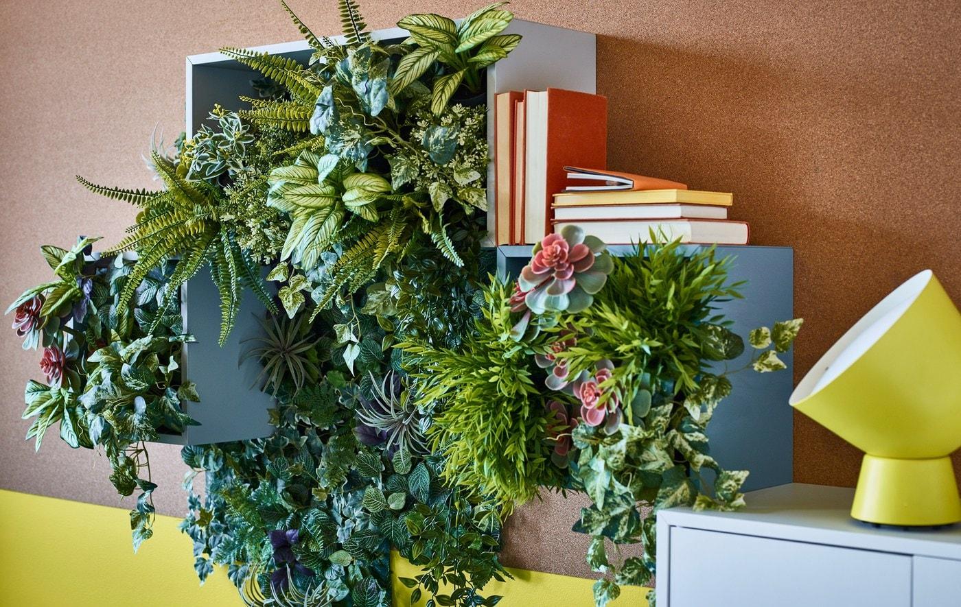 Plantas verdes artificiales en maceteros usadas para crear decoración de pared en cajas de almacenaje abierto.