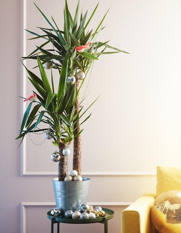Plante tropicale garnie de décorations blanches, dorées et gris argent et de quelques oiseaux