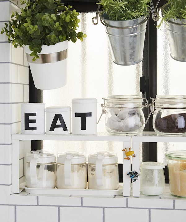 Plants and dry ingredients stored in pots and jars on a shelf insert.