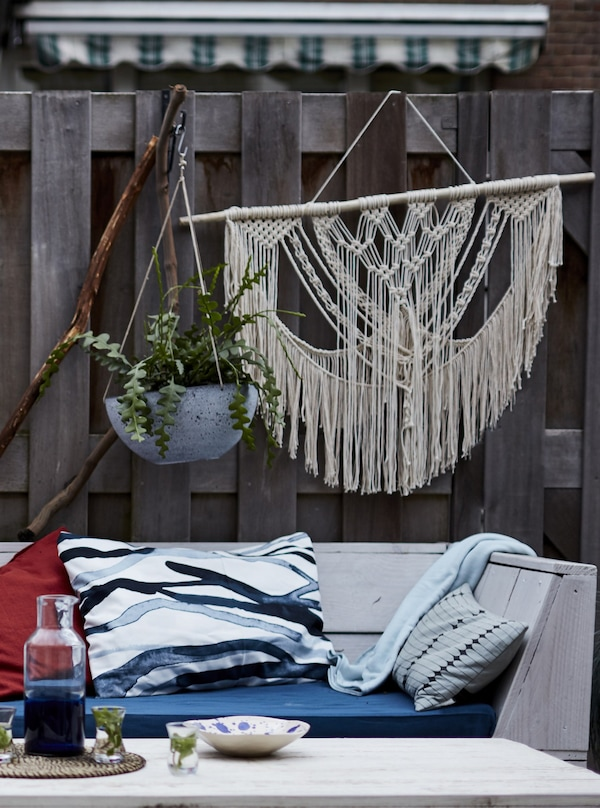 Plants and macramé hanging on a fence behind a wooden bench with cushions.