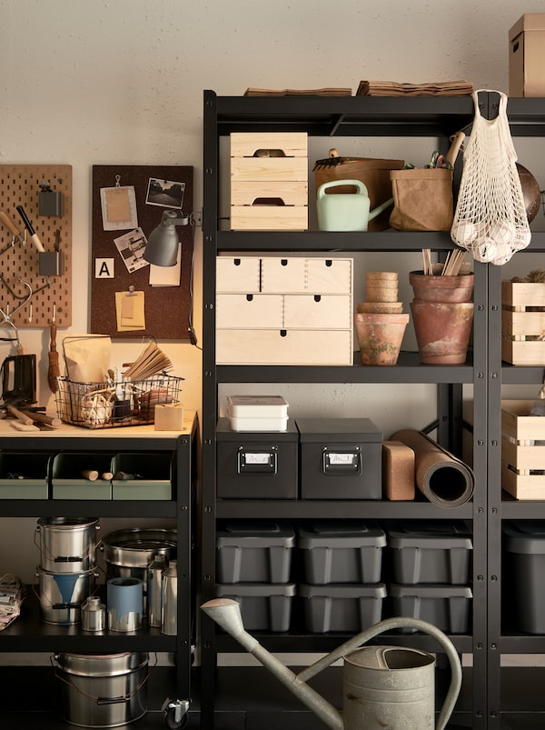 Plastic and wooden boxes, cardboard boxes and baskets made from textile inside BROR shelving unit organizing a garage wall.