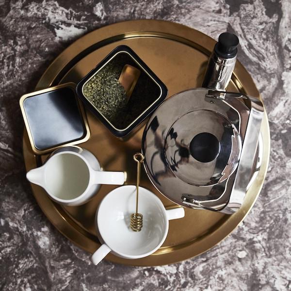 Plateau rond et doré, bouilloire, chope, pot à lait et feuilles de thé dans une boîte métallique.