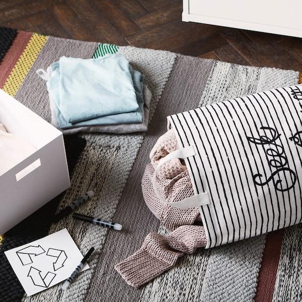 """Plátené vrecko s nápisom """"Hľadá sa nový majiteľ"""" s oblečením vo vnútri na koberci vedľa škatule, ceruziek a symbolu recyklácie."""