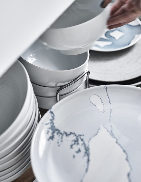 Plates and bowls stored in a deep drawer.