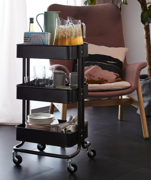 Plates, glasses and other tableware together with iced drink in jugs, all loaded on different levels of a trolley.